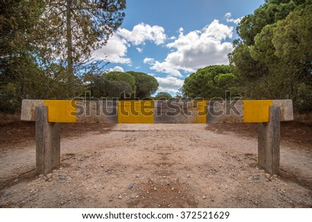 View of a wooden barrier demarcation to enter a pine forest. - stock photo