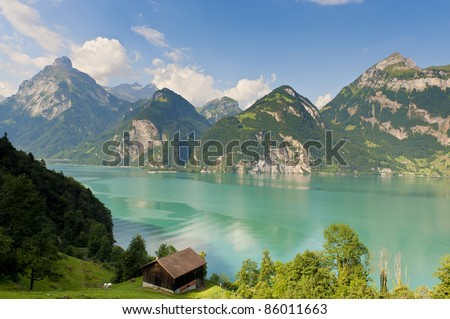 View of a wooden mountain cabin with a lake and mountain range in the background - stock photo