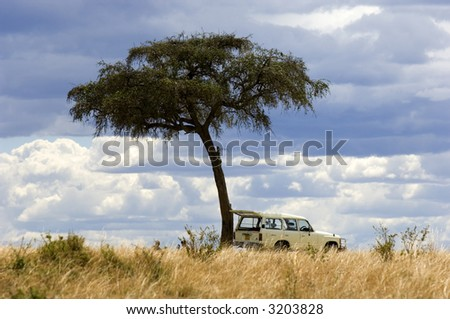 view of a 4X4 in the middle of a plain in the natural reserve of masai mara. - stock photo