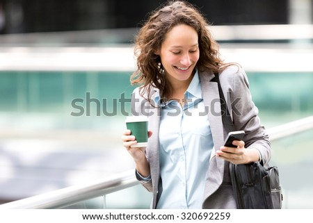 View of a Young attractive business woman using smartphone drinking coffee - stock photo