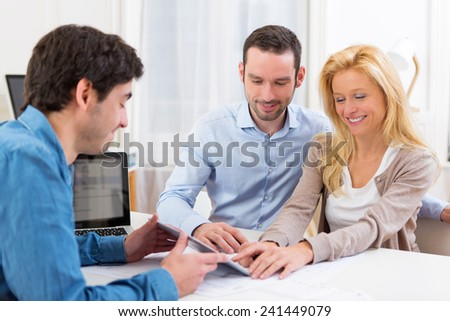View of a Young attractive couple signing contract on tablet - stock photo