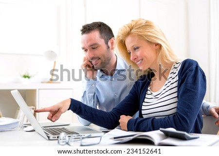 View of a Young attractive couple using laptop at home