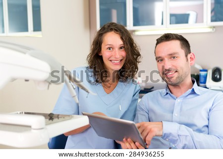 View of a Young attractive dentist explaning his work to a patient