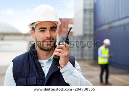View of a Young Attractive docker using talkie walkie at work - stock photo