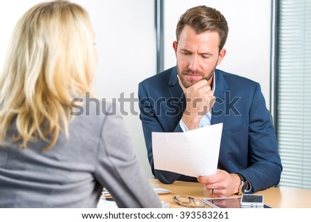View of a Young attractive employer analysing resume of woman - stock photo