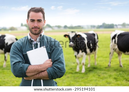 View of a young attractive farmer in a pasture with cows