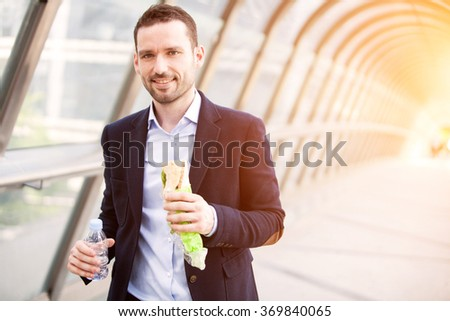 View of a Young attractive man eating fast his lunch - stock photo