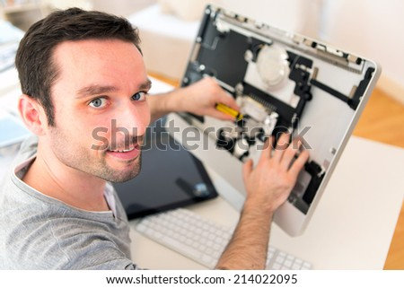 View of a Young attractive man repairing a computer - stock photo