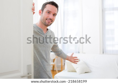 View of a Young attractive man welcoming you in his house - stock photo