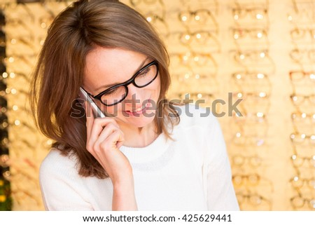 View of a Young attractive woman calling in an optician shop