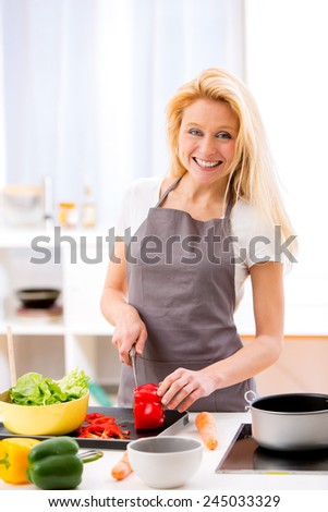 View of a Young attractive woman cooking in a kitchen
