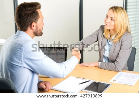 View of a Young attractive woman handshaking at the end of a job interview - stock photo