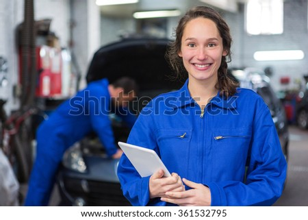 View of a Young attractive woman mechanic working at the garage
