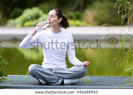 View of a Young attractive woman practising yoga in a park