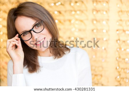 View of a Young attractive woman trying glasses at the optician