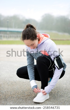 View of a Young attractive woman tying shoelaces before a running session - stock photo