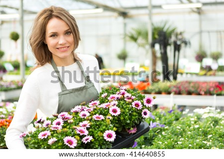 View of a Young attractive woman working at the plants nursery - stock photo