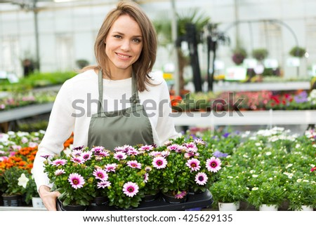 View of a Young attractive woman working at the plants nursery