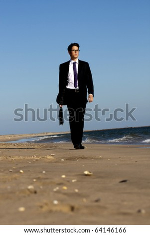View of a young business man walking down the beach.