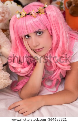 View of a young girl in a bedroom with a pink wig