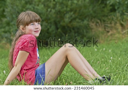 View of a young girl sitting on the grass - stock photo