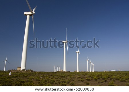 View of a young girl watching a field of windmills. - stock photo