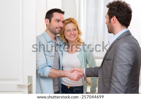 View of a Young happy couple handshaking real estate agent after signing contract