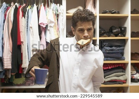 View of a young man putting on his jacket as he eats breakfast in his walk-in wardrobe - stock photo