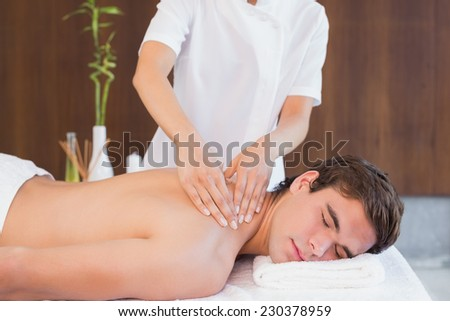 View of a young man receiving back massage at spa center - stock photo