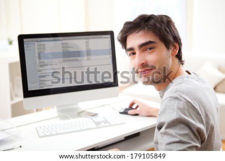 View of a Young smiling man in front of computer - stock photo