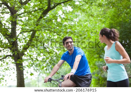 View of a Young sportive couple jogging at the park - stock photo