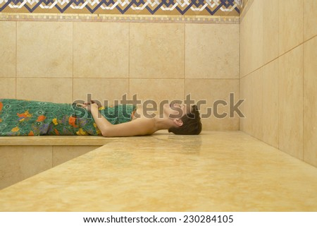 View of a young woman relaxing in a sauna - stock photo