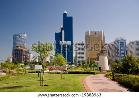 View of Abu Dhabi Skyline with gardens and small lighthouse in foreground - stock photo