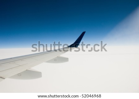 View of airplane wing out over a blue sky and white clouds. - stock photo