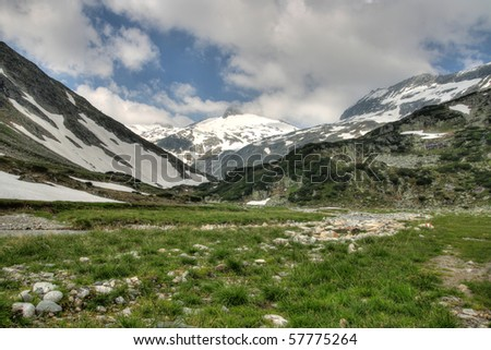 View of alps mountains with snow and dam under high mountain pasture