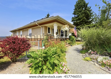 View of American craftsman house with lots of greenery and flower bed in the front.