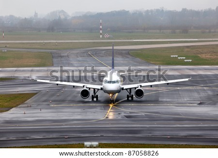 view of an aircraft preparing to take off on foggy runway - stock photo