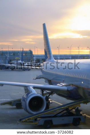 View of an airplane docked at an airport, ready for take off at sunset