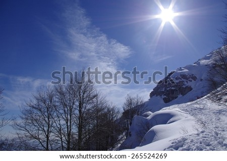 View of an alpine winter landscape with sunshine in a blue sky. - stock photo