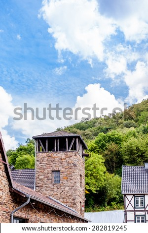 view of an ancient tower in the background a forest and beautiful blue sky - stock photo