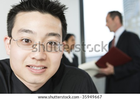 View of an Asian businessman with colleagues. - stock photo