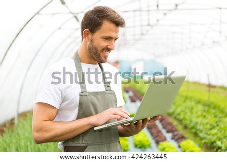 View of an attractive farmer in a greenhouse using laptop - stock photo