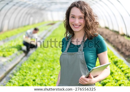 View of an attractive farmer in a greenhouse using tablet