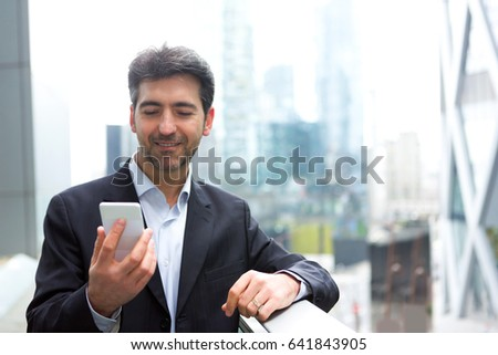 View of an Attractive middle aged business man checking email on his smartphone on the way to office
