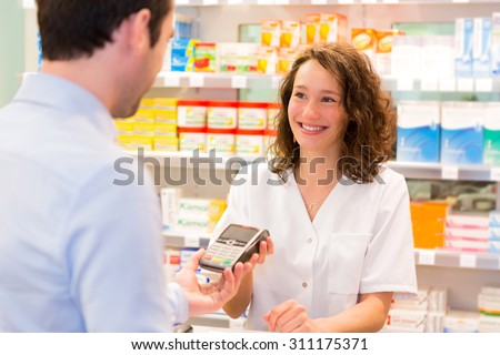 View of an Attractive pharmacist taking healt insurance card