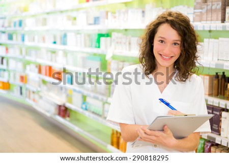 View of an Attractive pharmacist taking notes at work - stock photo