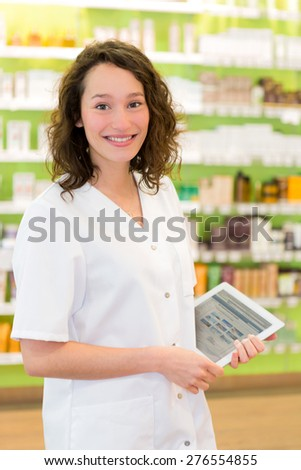 VIew of an Attractive pharmacist using tablet at work