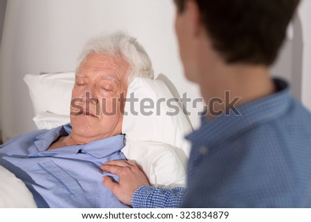 View of an elder man falling asleep and his relative  - stock photo
