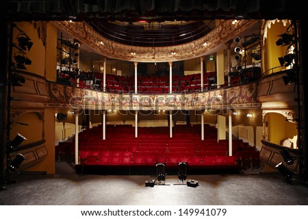 View of an empty theatre with red seats and balcony - stock photo