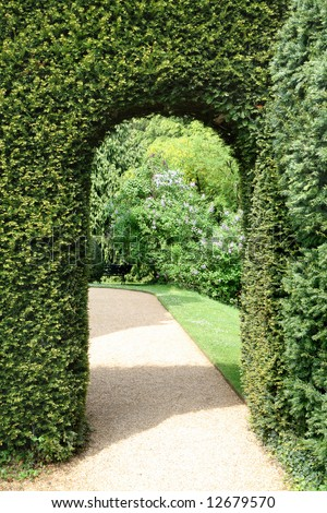 View of an English Mano Garden viwed through an archway though a Hedge - stock photo